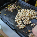 Big hands shelling little pistachios